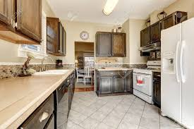 white kitchen cabinets with tile floor kitchen room brown cabinets tile floor and white appliances