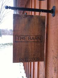 personalized sign hanging from metal post painted on barn wood
