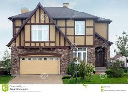 brown stone cottage with beige garage and roof royalty free stock