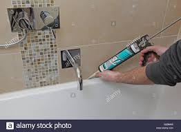 a workman uses a mastic gun to apply stone coloured silicone