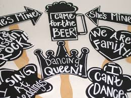 8 chalkboard photo booth props with phrases written chalk