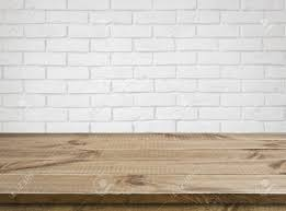 rough wooden texture table over defocused white brick wall