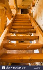 wooden stairs leading upstairs in handcrafted red cedar log home