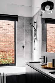 grey tiled bathroom with black fixtures and brick exposed walls