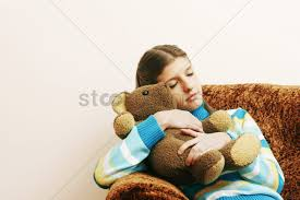 hugging her teddy bear while sleeping on couch stock