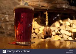 glass of beer on table with fireplace and logs in background stock