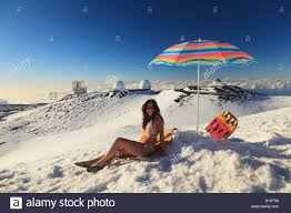 Hawaii travel umbrella images A woman in bikini sitting in the snow with beach umbrella with the jpg