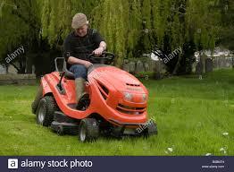 man on an orange ride on lawnmower cutting the grass in a church