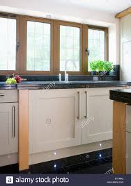 cream modern kitchen black granite worktop on cream fitted unit below window in modern