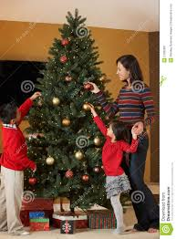 christmas mother and children decorating christmas tree stock