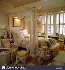 four poster bed with muslin drapes in traditional bedroom