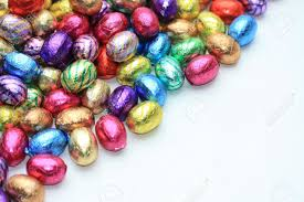a pile of colored easter chocolate eggs with copy space stock