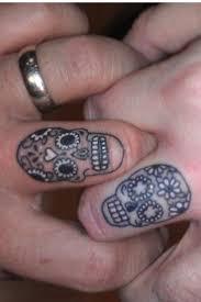 small sugar skulls tattoos on both fingers