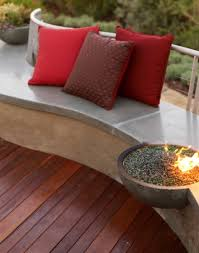 outdoor wooden floor with concrete bench also built in firepit