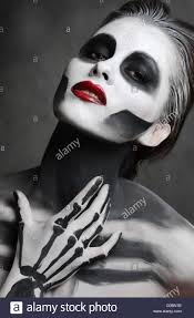 young woman with dead mask skull face art halloween face stock