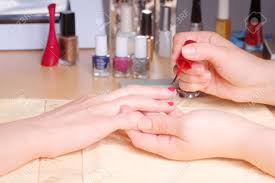 manicurist doing manicure client painting nails with red nail
