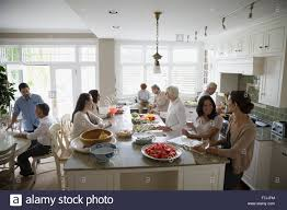 multi generation family gathering and cooking in kitchen stock