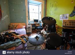 small messy teenager bedroom with electronic drums kit and guitar