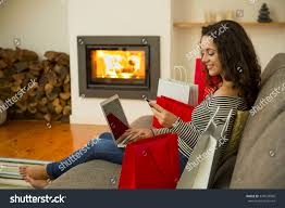 beautiful woman home warmth fireplace shopping stock photo
