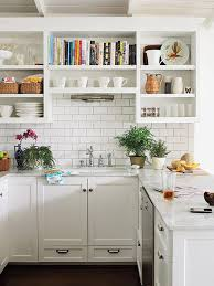 kitchen white wooden open shelves books sink faucet cups plates