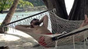 young man sleeping resting on hammock on beautiful beach stock