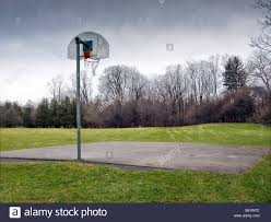 a vacant outdoor basketball court on a drab cloudy winter day with