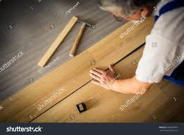 How To Replace A Damaged Laminate Floor Board Diy Repair Building And Home Concept Close Up Of Male Hands