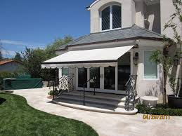 Beautiful Home Exterior Designs by Retractable Awning And Sliding Glass Door With Glass Walls In