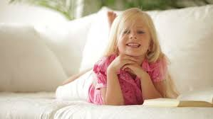 Happy Little Girl Lying On Sofa With Book And Smiling At Camera - Lying sofa 2