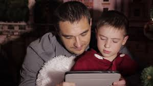 Brandon Flowers Son - 7 year old boy and his mum reading a bedtime story fix shot stock
