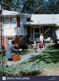 1950s father coming home kneeling arms extended boy running