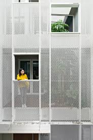 kc design studio adds perforated facade and atrium to skinny
