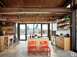 kitchen style orange bar stools wooden wall industrial kitchen orange bar stools wooden wall industrial kitchen design industrial open shelves hanging light stainless steel appliances countertops concrete flooring