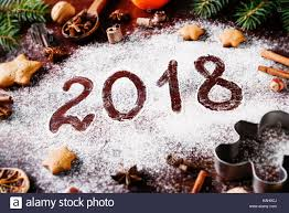 new year cookie cutters happy new year 2018 written on flour and christmas decorations stock
