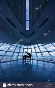 Glass Walls by A Grand Piano In The Corner Of A Room Of Glass Walls Overlooking