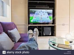 personal perspective man with feet up watching soccer game on tv