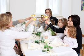 happy family toasting white wine at dining table in lawn stock