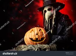 halloween background for poster for physician with green frightening plague doctor stands pumpkin medieval stock photo