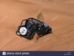 jeep dubai dubai united arab emirates jeep stuck in the sand stock photo