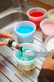 child mixing green foodcolouring in pot with plastic spoon to make