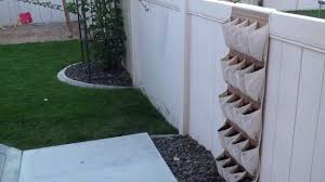 appealing vertical shoe storage installed at wooden fence which is