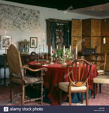 red chenille tablecloth in country dining room with antique chairs