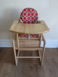 wooden high chair with padded cushion turns into table and chair