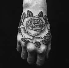 black and white rose tattoo on hand