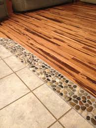 river rock in between wood and tile floors between the kitchen