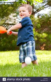 two and a half year old boy playing baseball in his backyard stock
