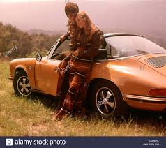 orange porsche 1970 1970s couple hugging standing by orange porsche woman striped