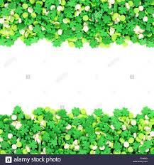 st patricks day frame of green shamrock candy sprinkles over white