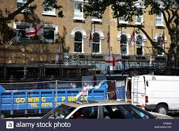 england flags flying from scaffolding outside high road house in