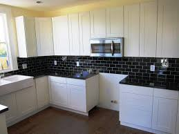 black subway tile kitchen backsplash with white cabinets amys office